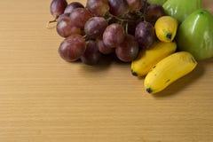Bananas, grapes of fresh fruit. On table Stock Image