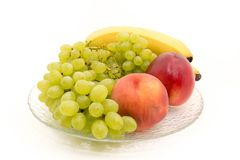 Bananas, grapes, peaches, nectarines, on a plate royalty free stock photography
