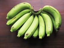 Bananas. A hand of bananas on wood table Stock Image