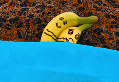 Bananas hugging each in bed. He is happy, she is sad Royalty Free Stock Photography