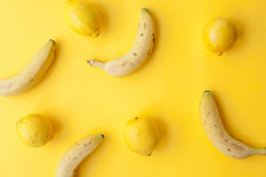 Bananas and lemons on yellow background Royalty Free Stock Images