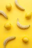 Bananas and lemons on yellow background Royalty Free Stock Photos