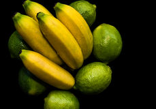 Bananas and Limes. Still life composition of bananas and limes Delicious organic fruit shot in studio on a black background Royalty Free Stock Photography
