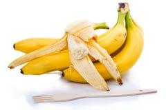 Bananas maduras e forquilha de madeira Fotos de Stock Royalty Free