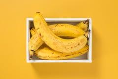 Bananas maduras em uma caixa no fundo amarelo brilhante Imagens de Stock