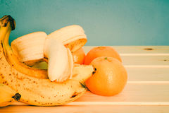 Bananas, mandarines on wooden table Stock Images