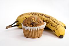 Bananas or Muffin?. Two ripe bananas in background - banana nut muffin in background.  Shallow depth Royalty Free Stock Images