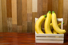 Bananas na cesta na tabela de madeira imagem de stock royalty free