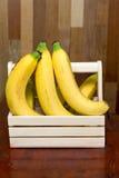 Bananas na cesta na tabela de madeira Foto de Stock