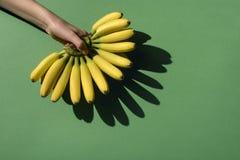 Bananas na mão preta imagem de stock