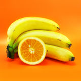 Bananas and Orange. Bunch of bananas and cuted orange on a bright orange background Stock Photo