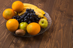 Bananas, oranges, apples, grapes are in dish Stock Images