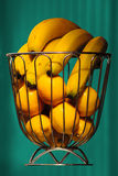 Bananas and oranges in iron basket with aquamarine curtain as background floating. Food still life photography for healthy life style Stock Photos