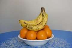 Bananas on oranges. Picture of a plate of juice oranges with a handful of bananas on top stock images