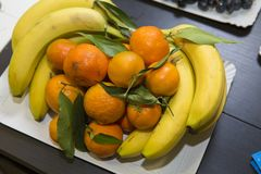 Bananas and oranges on a plate. At a party table royalty free stock photography