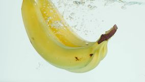 Bananas plunging into water on white background in slow motion Stock Photo