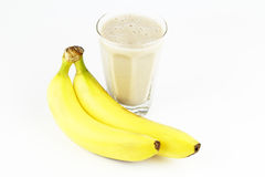 Bananas with Puree. Two long yellow sweet fruit are beside a glass of them liquified Stock Photo