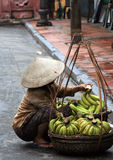 Bananas for sale. A lady selling bananas on a wet morning in Hoi An, Vietnam Royalty Free Stock Photos