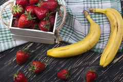 Bananas and strawberries in wooden box royalty free stock photo