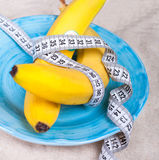 Bananas with a tape measure wrapped around it Royalty Free Stock Images