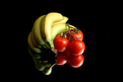 Bananas and tomatoes. Yellow bananas and red tomatoes on a vlack reflective mirror with reflections Royalty Free Stock Image
