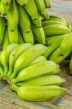 Bananas verdes em uma tabela de madeira Fotos de Stock Royalty Free