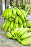 Bananas verdes em uma tabela de madeira Imagens de Stock