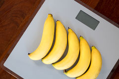 Bananas on weighing machine Stock Photos