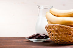 Bananas in a wicker basket on a background of chocolate and milk. Bananas in wicker basket on a background of chocolate and milk Royalty Free Stock Photo
