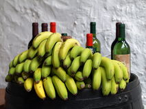 Bananas and wine bottles. Stock Photos