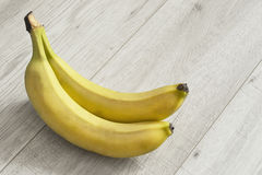 Bananas on wooden floor Stock Photos