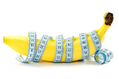Bananas wrapped with measuring tape. Royalty Free Stock Photography