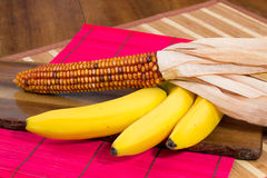 Bananas and yellow corn on colorful wooden boards Stock Photos