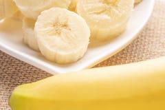Banane affettate ed intere su un piatto bianco e su un vecchio tetto di legno fotografia stock