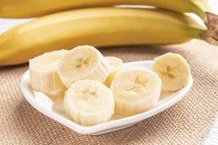 Banane affettate ed intere su un piatto bianco e su un vecchio tetto di legno fotografie stock libere da diritti
