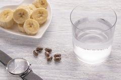 Banane affettate ed intere Su un piatto bianco Sulla vecchia tavola di legno Vetro appannato con acqua pulita fotografie stock libere da diritti