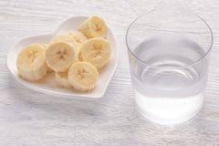 Banane affettate ed intere Su un piatto bianco Sulla vecchia tavola di legno Vetro appannato con acqua pulita immagine stock
