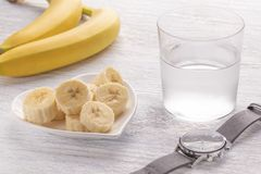 Banane affettate ed intere Su un piatto bianco Sulla vecchia tavola di legno Vetro appannato con acqua pulita immagini stock