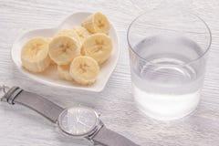 Banane affettate ed intere Su un piatto bianco Sulla vecchia tavola di legno Vetro appannato con chiara acqua Chiuda su su un fon fotografie stock