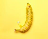 banane avec la bande de mesure sur un fond jaune Images libres de droits