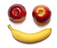 Banane avec la pomme rouge sur le blanc Photos stock