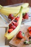 Banane con le fragole ed il cioccolato Immagini Stock