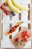 Banane con le fragole ed il cioccolato Immagini Stock Libere da Diritti