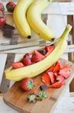 Banane con le fragole ed il cioccolato Immagine Stock