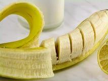 Banane coupée en tranches, citron et une bouteille de yaourt photographie stock libre de droits