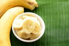 Banane dans une tasse au-dessus d'une feuille de banane Photos stock