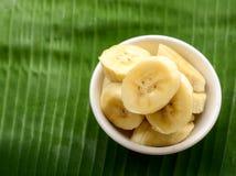 Banane dans une tasse au-dessus d'une feuille de banane Photographie stock libre de droits