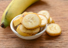 Banane dans une tasse au-dessus d'une table Image stock