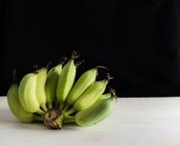Banane di natura morta sulla tavola bianca e sul fondo nero Fotografie Stock Libere da Diritti