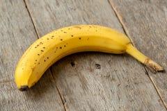 Banane, die auf altem hölzernem Hintergrund liegt lizenzfreie stockfotos